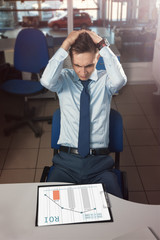 Manager in office horrified/ Manager of the office employee in a shirt and tie is horrified over the ROI schedule with a drop in efficiency and sales. Holds his hair because of stress.