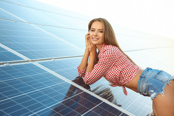 Beautiful young woman near solar panels outdoors