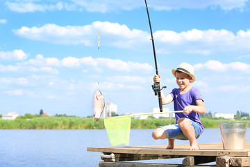 Cute boy fishing on summer day