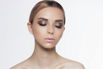 Beauty portrait of the woman on the isolated white background. The girl shows fashionable cosmetics and gentle care face skin.
