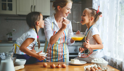Happy family mother and children twins   bake kneading dough in kitchen