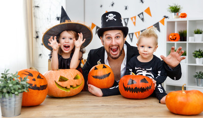 family father and children in costumes   to halloween with pumpkin Wall mural