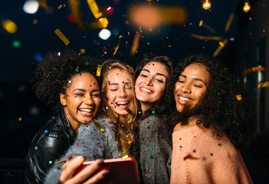 Group of happy women taking selfie on mobile phone, standing outdoors at night