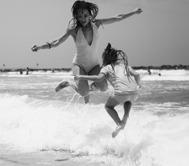 Portrait of happy  real beautiful young girls jumping on seaside