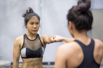 Photo sur Toile Ecole de Yoga young asian athletic women in sportswear punching and looking herself in the mirror