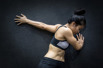 young asian woman wearing sportswear stretching her arm on black wall in fitness gym, exercise for healthy lifestyle concept