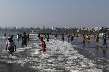Children enjoy their first visit to the sea, during a special program organised by the Ministry of Education at Agua Dulce Beach in Lima
