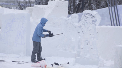View of sculptor carving ice. Movement. Cut ice with a chainsaw. Cut and make snow sculpture. Chopping iced water with an axe. Ice Sculpture Carving. V-LOG