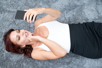 Happy young woman texting message on carpet