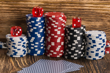Stacks of poker chips with cubes and cards on a wooden background
