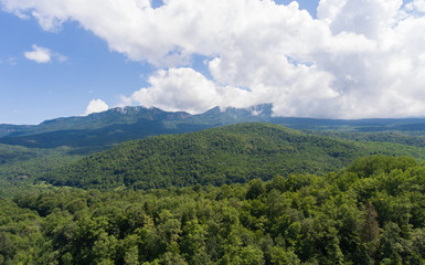 Summer mountain landscape. Forested mountains and clouds.