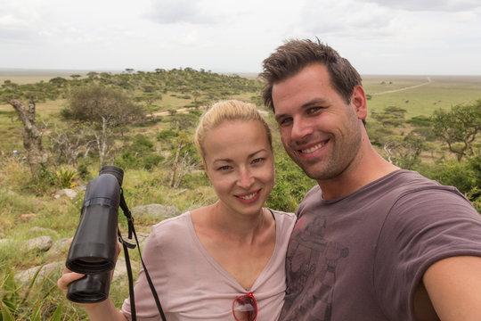 Casual adult couple taking selfie on african wildlife safari in Serengeti national park, Tanzania, Africa.