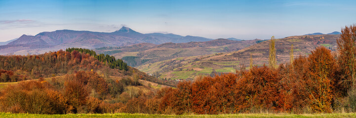 gorgeous autumn countryside panorama in mountains. forest with red foliage on rolling hills, village in valley and mountain ridge with high peak in a distance. Beautiful landscape in Carpathians