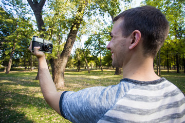Young man taking selfie on retro camera in city park
