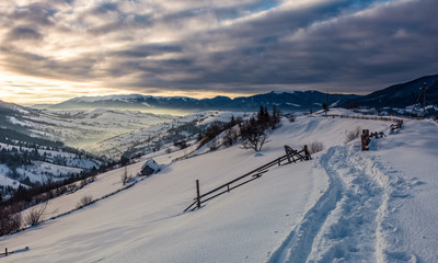 beautiful countryside in mountains. path in a snow near the wooden fence over the village and rural fields on hillsides covered with snow at sunrise