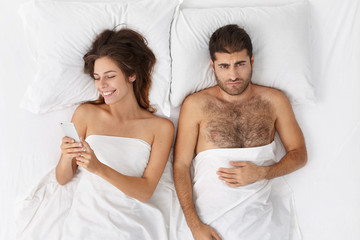 High angle view of unhappy frustrated bearded man having offended look, lying in bed side by side with his internet addicted wife who is chatting with friends or browsing social networks, ignoring him