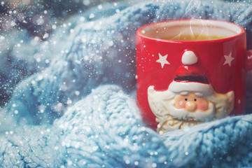 Winter background - red cup with santa claus and woolen scarf