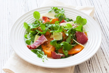 Salad with pumpkin, bacon , cheese and arugula