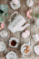 tea set in composition with flowers and marshmallows. Coffee mug on a saucer, a teapot and a sugar bowl. Filmed in the interior
