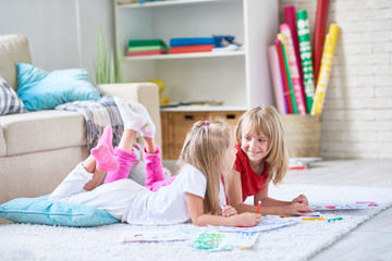 Portrait of two happy little girls coloring pictures together lying on floor on thick plush carpet in cozy living room at home