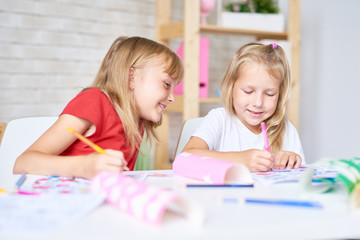 Portrait of two cute little sisters coloring pictures together sitting at table in playing room and smiling