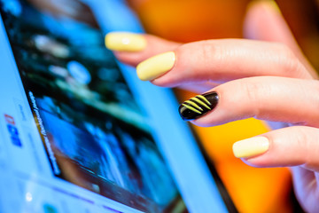 Closeup female hands fingers with yellow nails over tablet screen