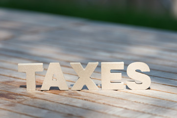 High Angle View Of  Tax Word On Wooden Background