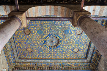 Ornate ceiling with blue and golden floral pattern decorations frammed throught huge arch and two columns at Sultan Barquq mosque, Al Moez Street, Cairo, Egypt