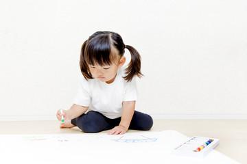 お絵描きをする幼い女の子