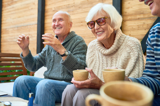 Cheerful senior friends gathered together at cozy small patio and remembering funny stories from their past, they wearing knitted sweaters and warming themselves with herbal tea