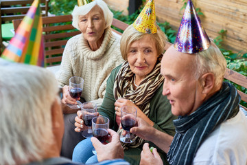 Group of elderly friends wearing warm clothes holding glasses with red whine in hands and chatting with each other while having outdoor birthday party