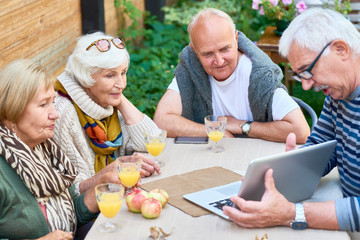Two senior couples spending weekend together at backyard: they looking through photos on laptop and enjoying freshly squeezed juice