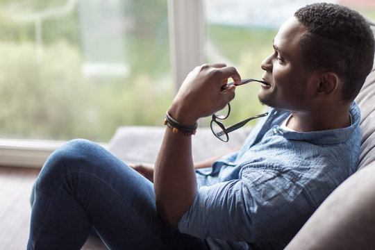 Smiling black man lying and relaxing on the couch at home in the living room