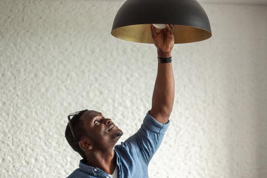 African man changing light bulb , installing a fluorescent light bulb