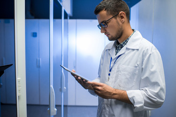 Side view portrait of young network engineer looking at digital tablet while standing between server cabinets in supercomputer research center