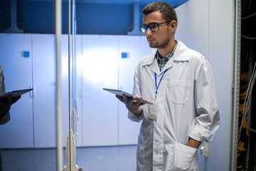 Portrait of young network engineer holding digital tablet while standing between server cabinets in supercomputer research center