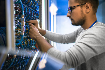 Side view portrait of young man wearing glasses connecting cables in server cabinet while working with supercomputer in data center