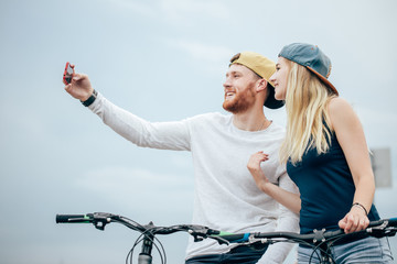 happy couple with bicycle taking selfie outdoors