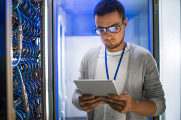 Portrait of young man using digital tablet standing by server cabinet while working with supercomputer in blue light
