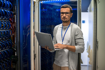 Portrait of young man holding laptop and looking at camera standing by server cabinet while working with supercomputer in blue light