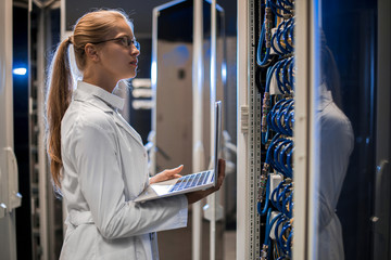 Side view portrait of blond female scientist wearing lab coat using laptop while working with supercomputer standing by server cabinets