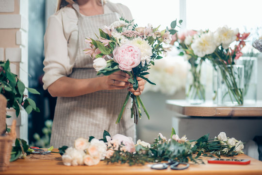 Small business. Male florist unfocused in flower shop. Floral design studio, making decorations and arrangements
