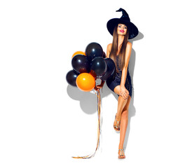 Halloween party girl. Sexy witch holding black and orange air balloons. Beautiful young woman in witches hat and costume