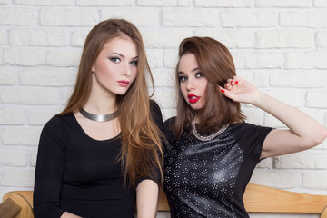 two beautiful young girls in black dresses sit on the bench and gossip