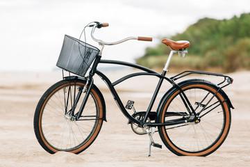 Pretty bicycle parked on beach. Retro bike near the sea