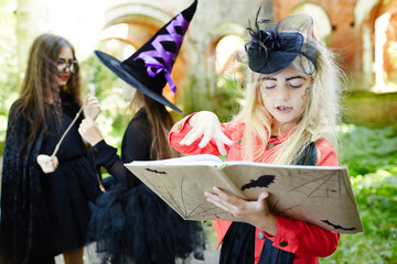 Cute girl in halloween attire looking through spell book and choosing magic-spell