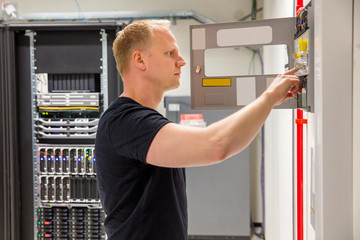 Confident Male Technician Checking Fire Panel In Datacenter