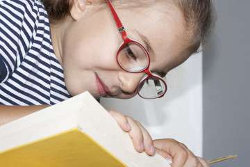 Girl with glasses reading a big yellow book