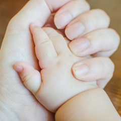 hands of the mom and her baby