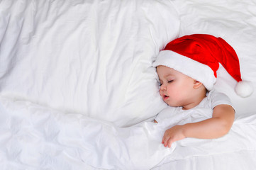 little baby lying on white linen in the Santa hat and clock show five minutes to eleven